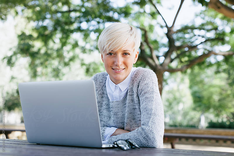 Portrait of a woman sitting in the park with her laptop.  by BONNINSTUDIO for Stocksy United