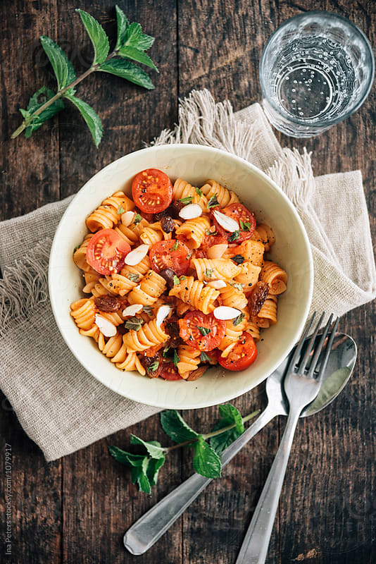 Food: Sicilian Pasta (Fusili) with tomato, almond,raisin, basil and mint by Ina Peters for Stocksy United