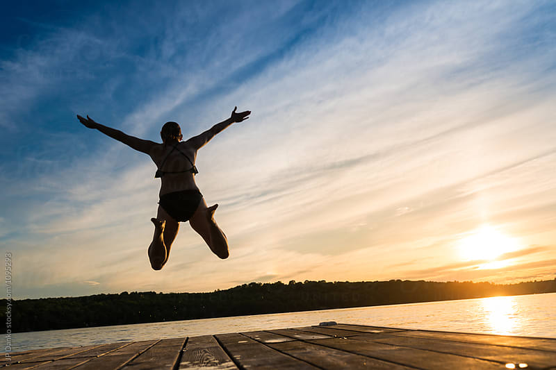 Fun Woman Jumping Into Warm Summer Cottage Lake At Sunset from Dock by JP Danko for Stocksy United