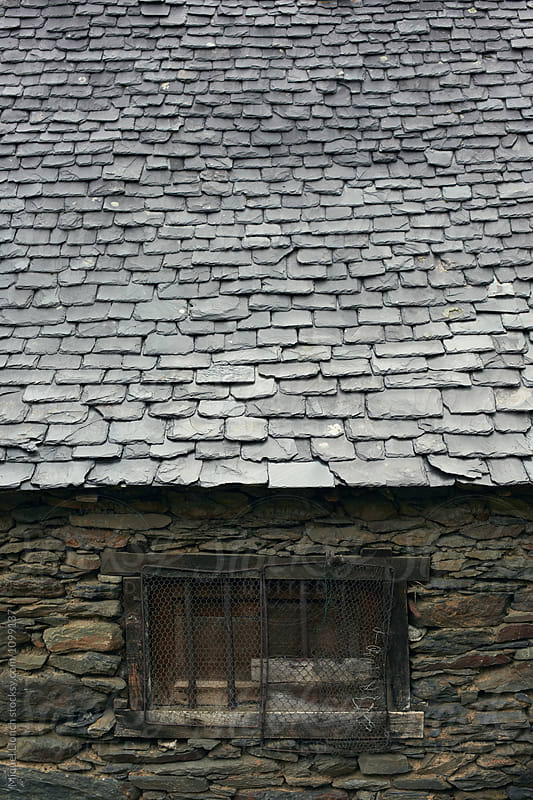 Detail of an slate roof of an old stone house by Miquel Llonch for Stocksy United