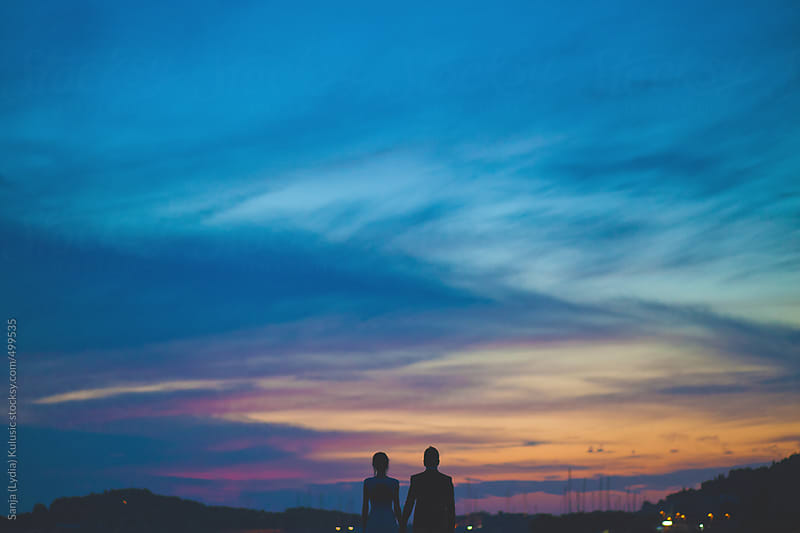 Love couple looking at the sunset by Sanja (Lydia) Kulusic for Stocksy United