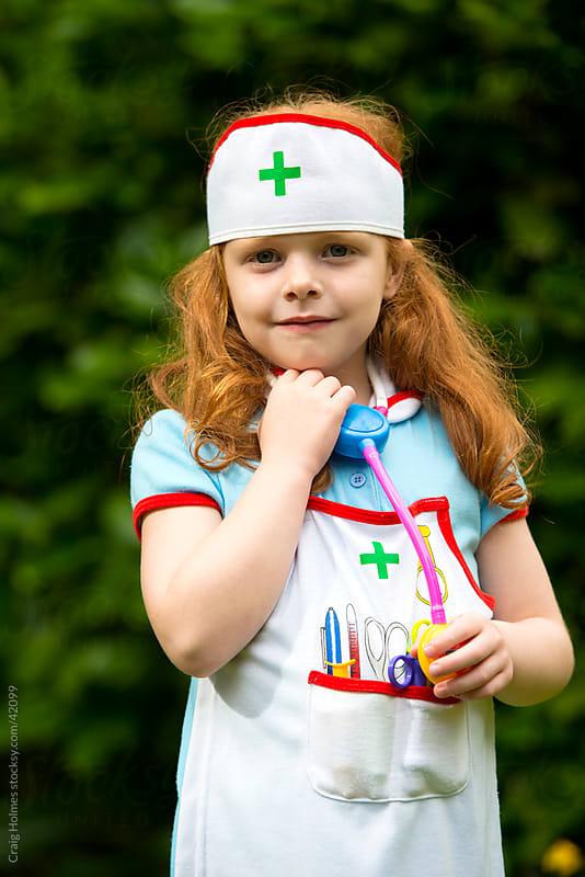 6 year old girl role playing as a nurse by Craig Holmes for Stocksy United