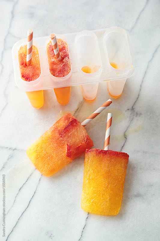 Melting orange popsicles on marble top by Sandra Cunningham for Stocksy United