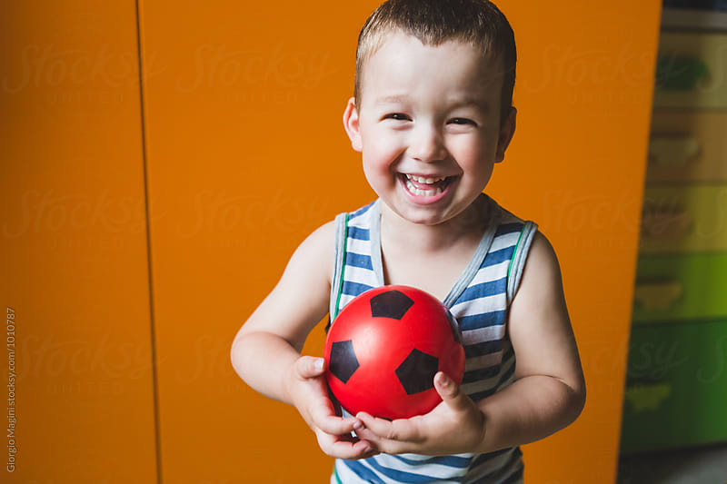 Happy Male Toddler at Home Playing with a Small Red Ball by Giorgio Magini for Stocksy United