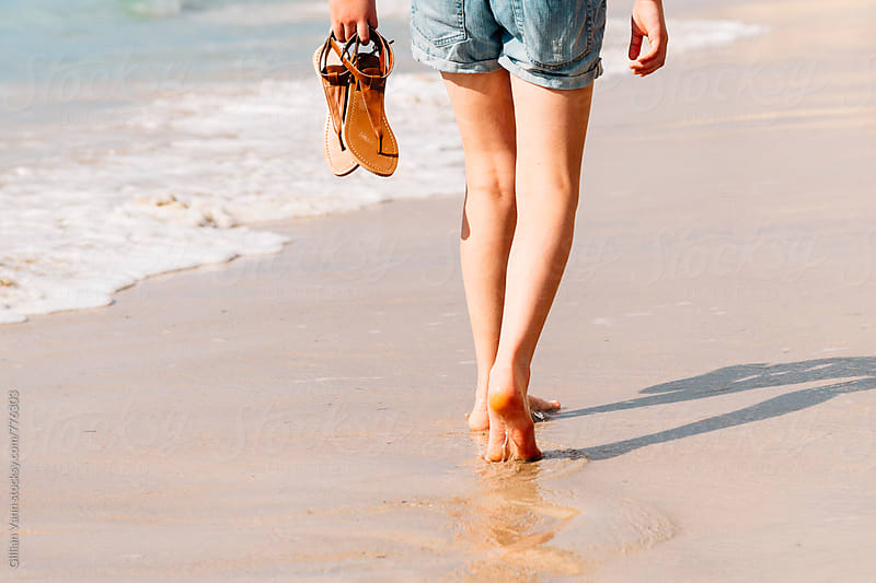 a teenager walking barefoot at the beach by Gillian Vann for Stocksy United