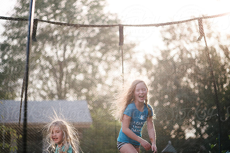 Two girls jump on a trampoline at sunset. by Kelsey Gerhard for Stocksy United