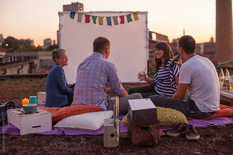 Friends in a Rooftop Open Air Cinema by Mosuno for Stocksy United