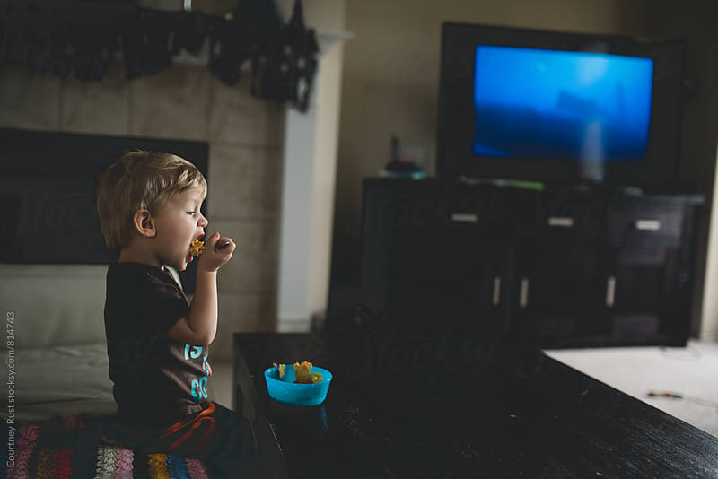 cereal in front of the tv by Courtney Rust for Stocksy United