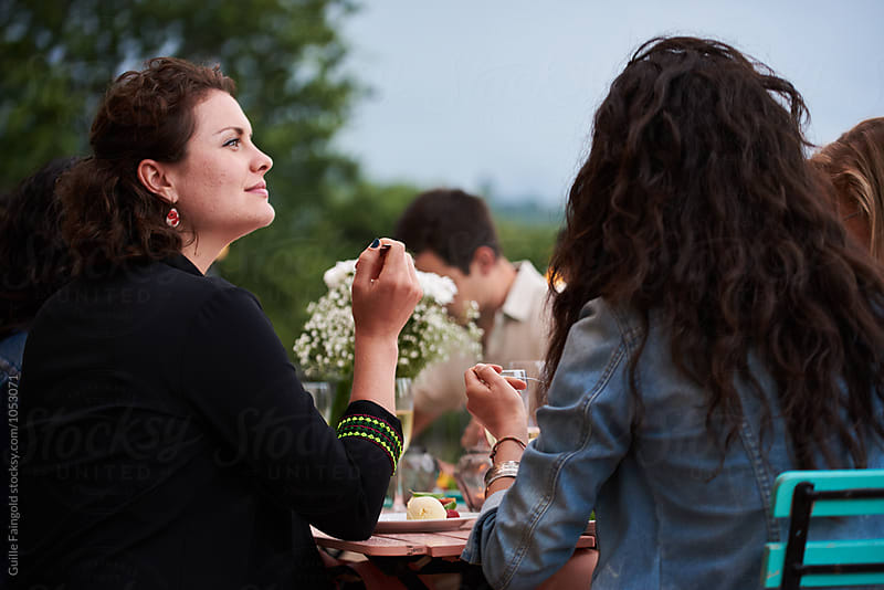 Friends eating dinner on terrace by Guille Faingold for Stocksy United