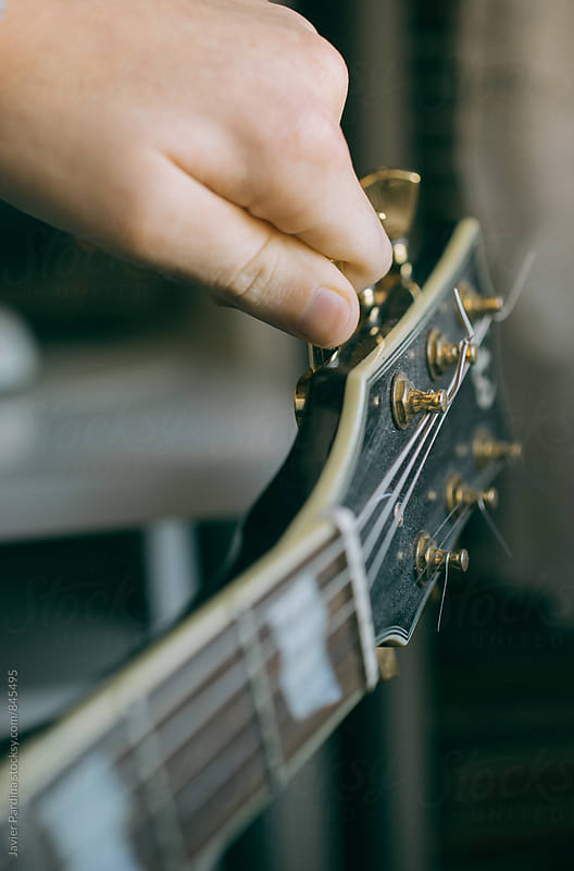 man playing guitar  by Javier Pardina for Stocksy United
