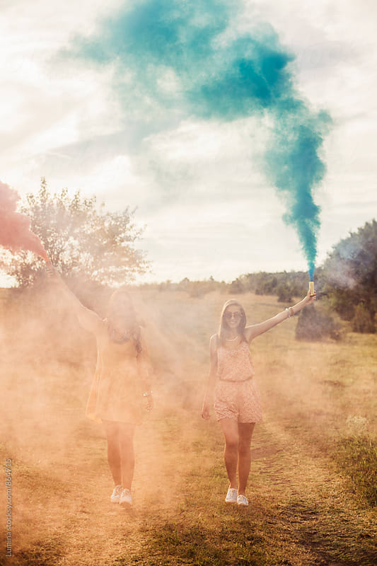 Happy Girls Holding Smoke Bombs by Lumina for Stocksy United