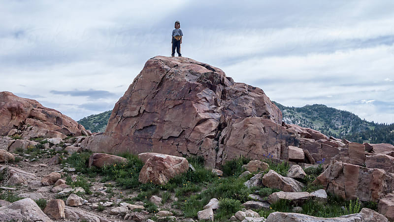 Small boy standing on a large boulder by Adam Nixon for Stocksy United