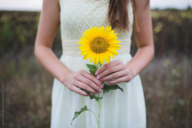 Young woman holding a sunflower by Jovana Rikalo for Stocksy United