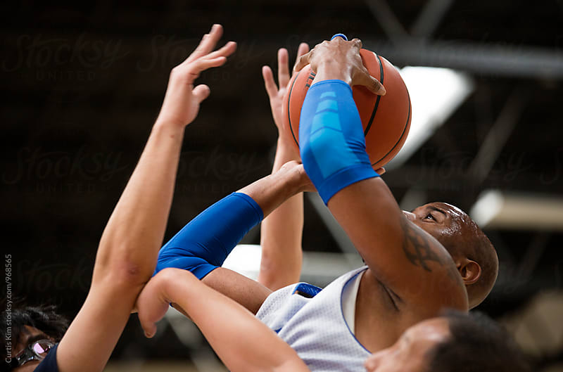 Basketball player shooting with hands blocking the ball by Curtis Kim for Stocksy United