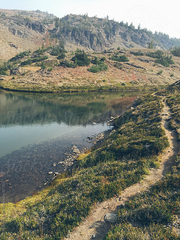 Hiking trail along edge of small alpine lake in the Central Cascades by Paul Edmondson for Stocksy United