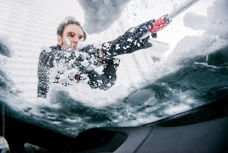 Man removes snow from the windshield of his car by Cara Dolan for Stocksy United