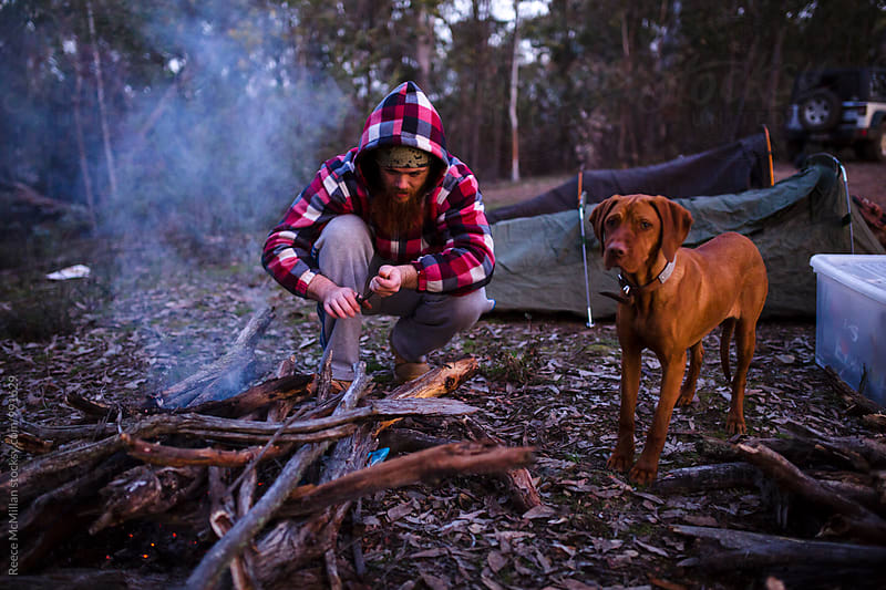 A man and his dog starting a morning fire by Reece McMillan for Stocksy United