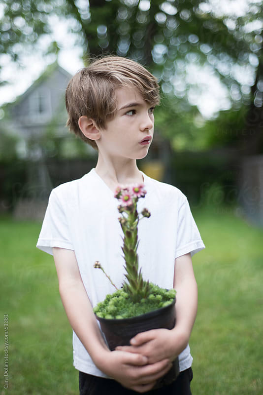 Boy holding a hens and chicks plant in his arms in the backyard  by Cara Dolan for Stocksy United