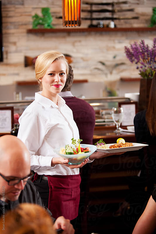 Sushi: Pretty Waitress Serving Food to Customers by Sean Locke for Stocksy United