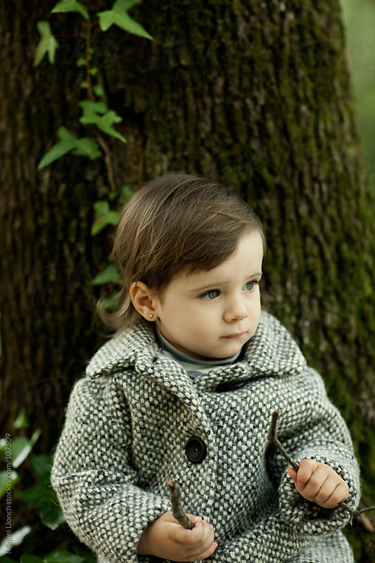 Little girl with coat and tree background by Miquel Llonch for Stocksy United