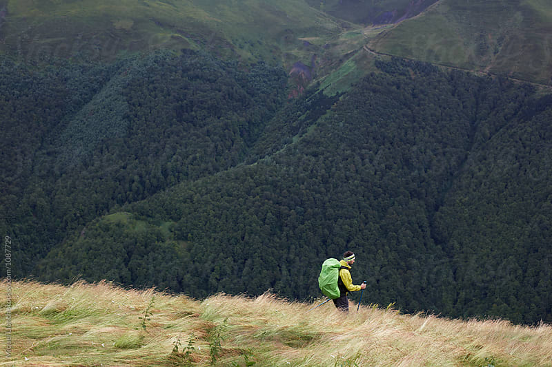 Backpacker with rain gear going down a valley by Miquel Llonch for Stocksy United
