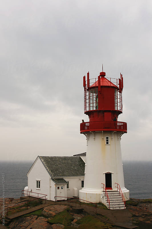 Lindesnes Fyr, Norway, a red and white lighthouse with the misty sea in the background.  by Kaat Zoetekouw for Stocksy United