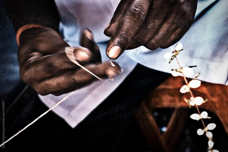 Hands of Indian man crafting flower chains in close-up by Soren Egeberg for Stocksy United