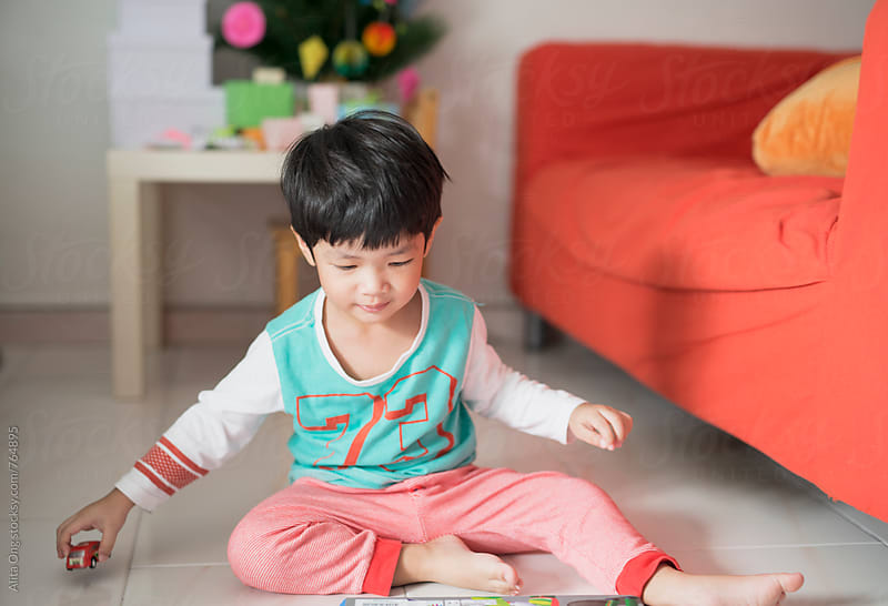 Boy sitting on the floor playing with toy car by Alita Ong for Stocksy United