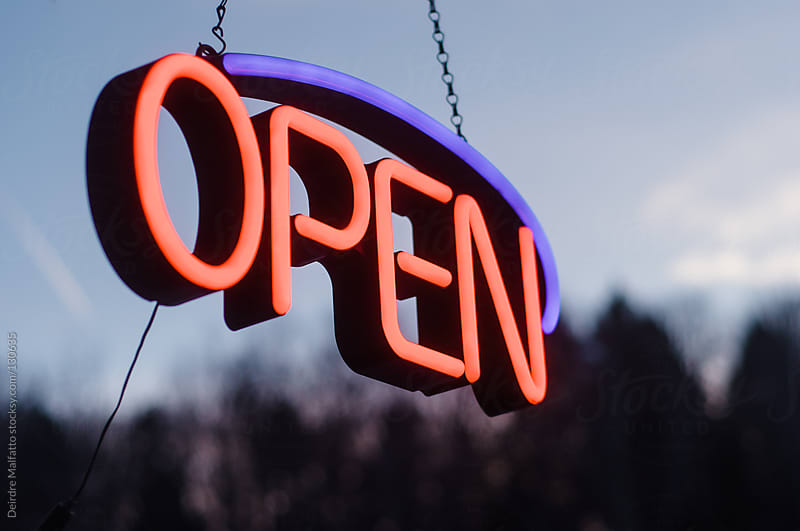 neon open sign hanging outside in the dusk by Deirdre Malfatto for Stocksy United