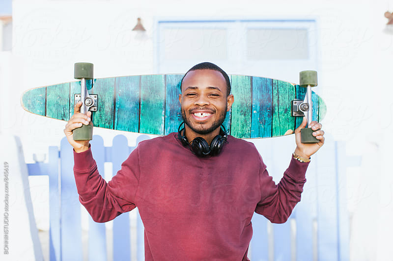 Portrait of a smiling man holding his longboard outside. by BONNINSTUDIO for Stocksy United