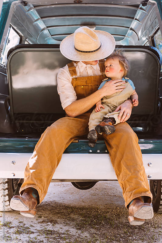 Father and Son in Back of Old Truck by Geoffrey Hammond for Stocksy United