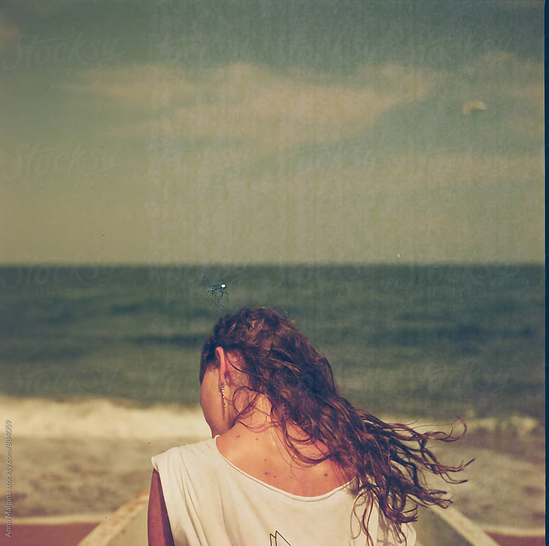 A back portrait of young woman in front of sea by Anna Malgina for Stocksy United
