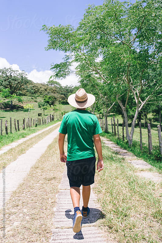 Young man with straw hat walking on a path in the countryside seen from behind by Alejandro Moreno de Carlos for Stocksy United