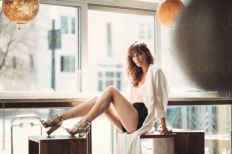 A beautiful model relaxing by a counter at a lounge by Ania Boniecka for Stocksy United