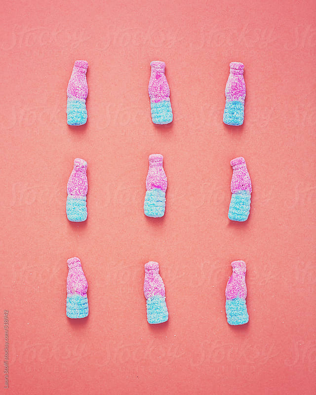 Bottle shaped gummy candies on pink background by Laura Stolfi for Stocksy United