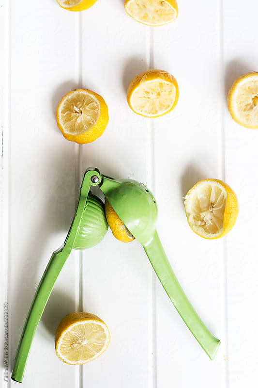 squeezed lemons with green juicer by Gillian Vann for Stocksy United