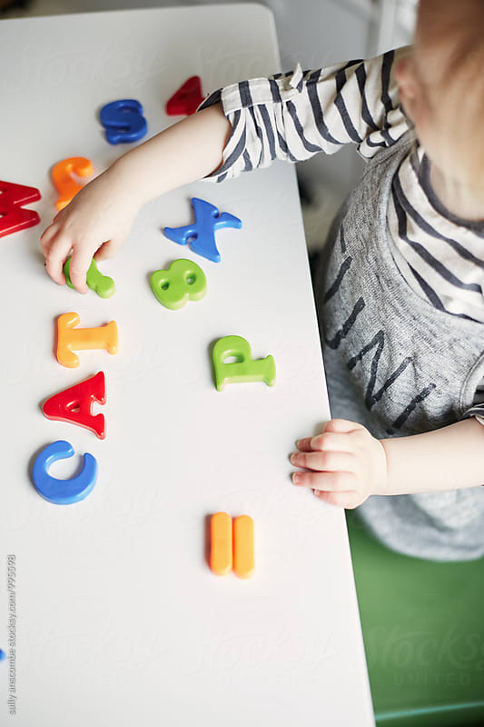 Little toddler girl playing with coloured letters by sally anscombe for Stocksy United