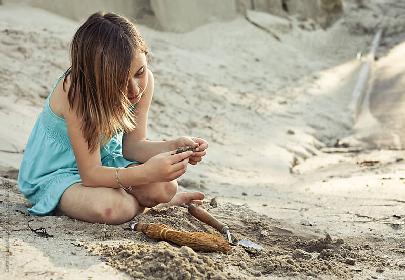 Little girl with a skinned knee digging for fossils by Carolyn Lagattuta for Stocksy United