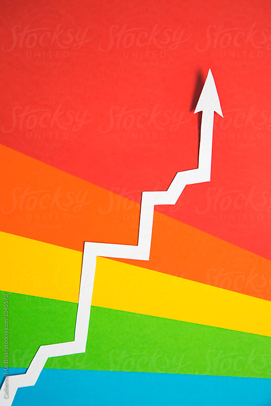 White arrow heading upward on rainbow background... by Catherine MacBride for Stocksy United