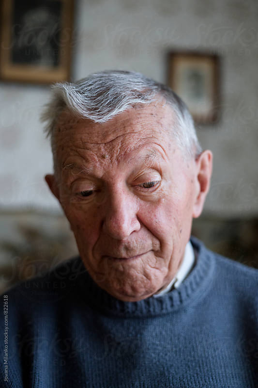 Portrait of a gray haired senior sitting alone in his living room  by Jovana Milanko for Stocksy United
