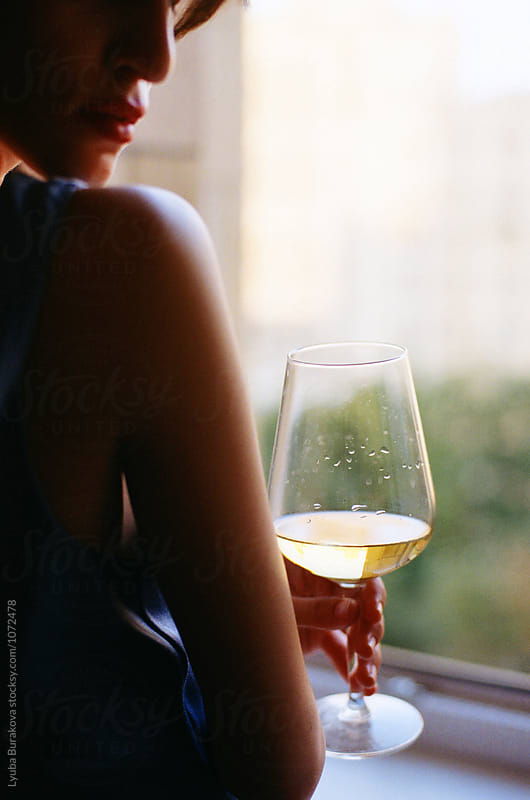 Woman holding glass of white wine by Lyuba Burakova for Stocksy United