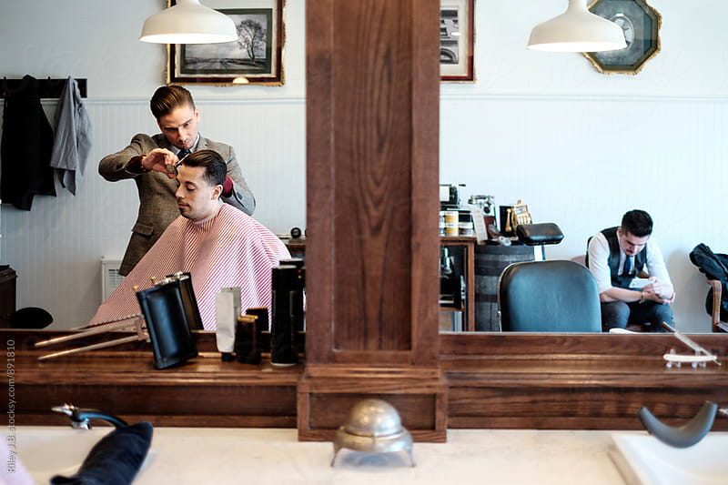 A barber shears a client's hair reflection. by Riley J.B. for Stocksy United