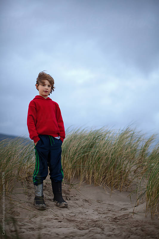 Windblown boy on a sand dune by Carleton Photography for Stocksy United
