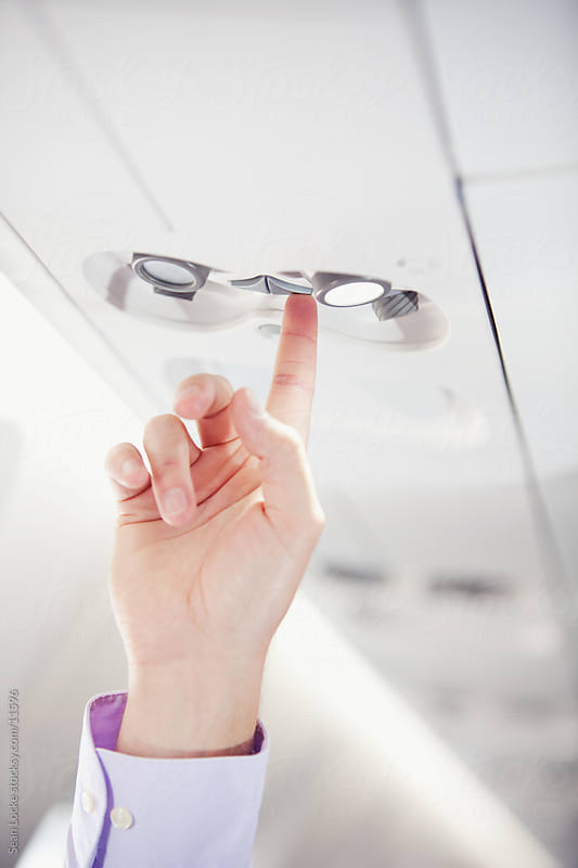 Airplane: Passenger Pushes Attendent Call Button by Sean Locke for Stocksy United