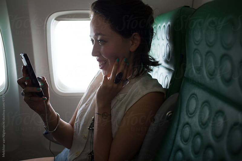 Young asian woman sits in airplane watching her cell phone by Melchior van Nigtevecht for Stocksy United