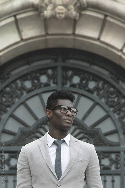 African young businessman with rimmed glasses in outdoors. by BONNINSTUDIO for Stocksy United