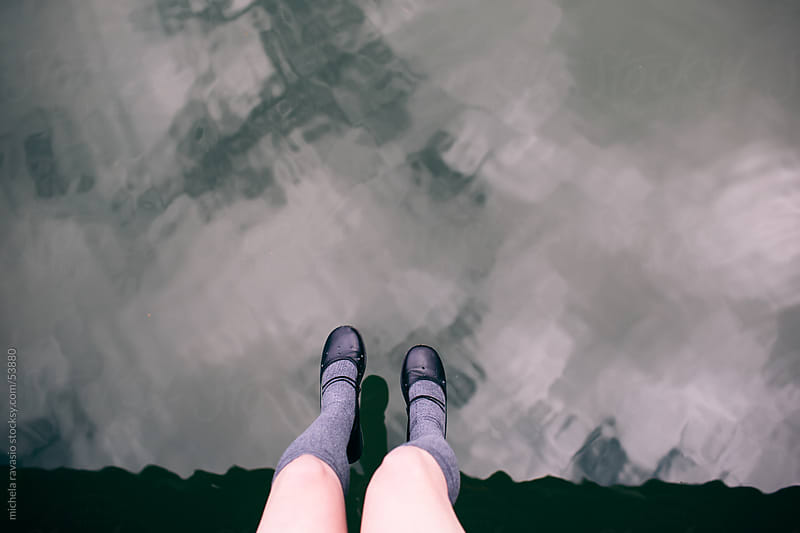 Legs dangling over the river by michela ravasio for Stocksy United