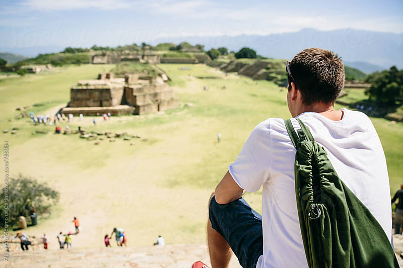 Back view of young man traveler sitting down contemplating ancient ruins landmark in Mexico by Alejandro Moreno de Carlos for Stocksy United