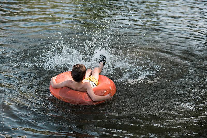 little boy floating on lake by Léa Jones for Stocksy United