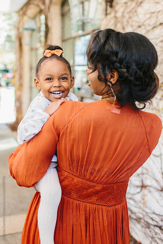 An adorable girl toddler on her mother's hip and smiling by Kristen Curette Hines for Stocksy United